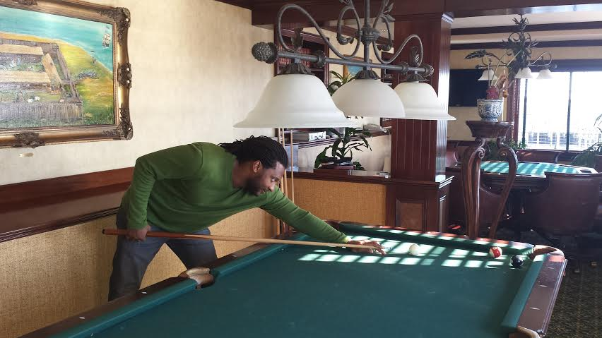Cousin mars playing pool in one of Saybrook Point Inn's lounges that often doubles as a groom + groomsmen hangout on the big day.